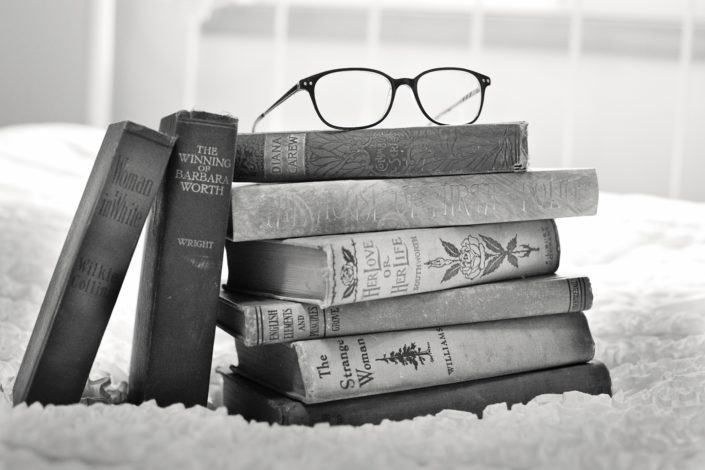 Stack of vintage books with glasses