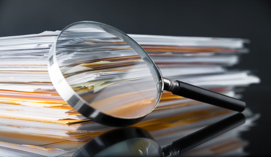 magnifying glass over stack of papers